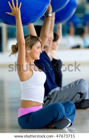group of people at the gym smiling with pilates balls - stock photo