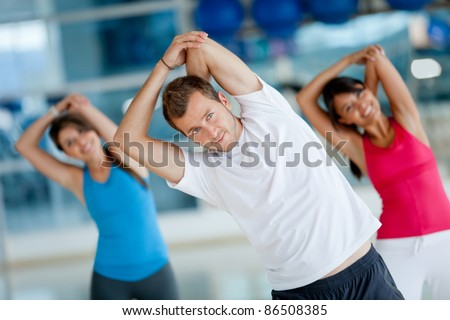 Group of people at the gym stretching their arms - stock photo