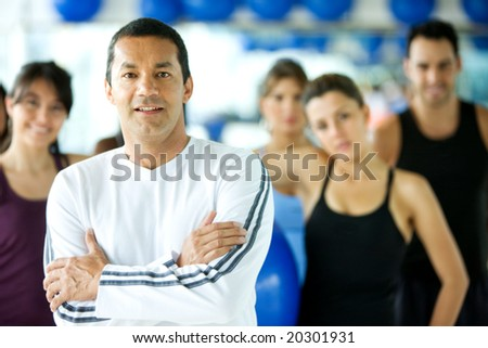 group of people at the gym with the trainer leading - stock photo