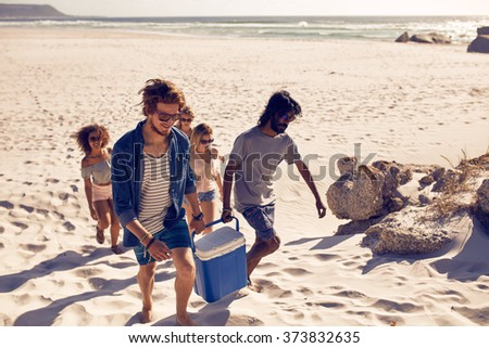 Group of people carrying cooler to party on beach. Two young men carrying cooler with female friends at the back, looking for a spot of picnic on the sea shore. - stock photo
