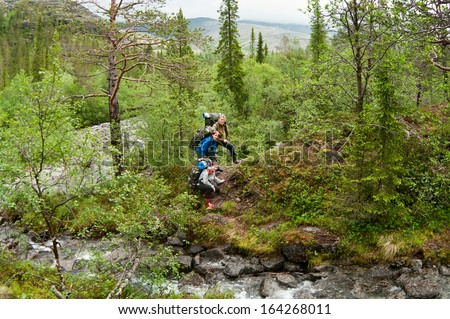 Group of people climbing and trekking in hills - stock photo
