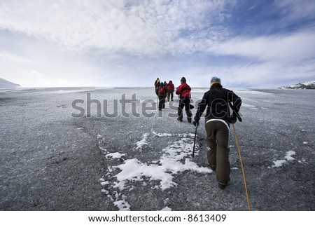 Group of people climbing glacier - stock photo