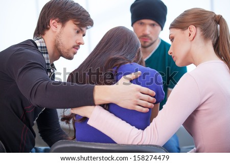 Group of people comforting upset woman. Hugging from the both sides  - stock photo