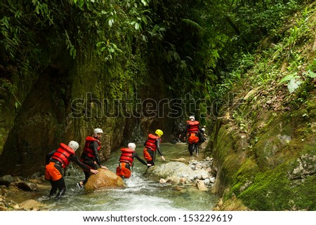 Group of people crawling into canyons of Llanganates nation park in Ecuador. - stock photo