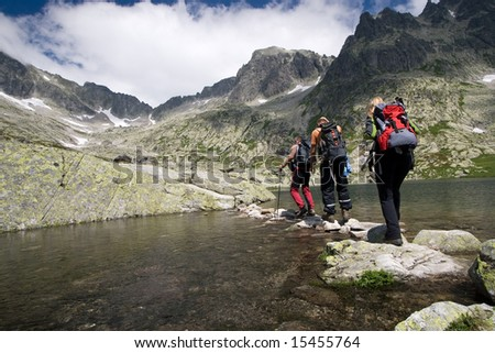 Group of people crossing mountain pond in Tatra Mountains, Slovakia - stock photo