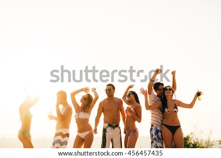 Group of people dancing at summer beach party