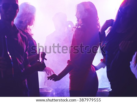 Group of people dancing in night club - stock photo