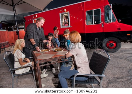 Group of people dining at pizza canteen outside - stock photo