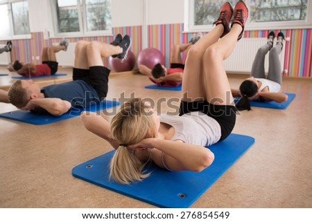 Group of people doing crunches on exercise floor mat - stock photo