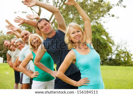 Group of People doing flexibility exercises.Focus on foreground. - stock photo