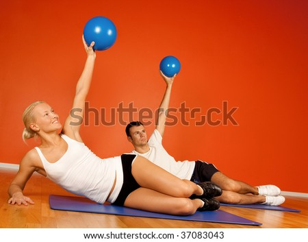 Group of people doing stretching exercise with fitness balls in fitness room - stock photo