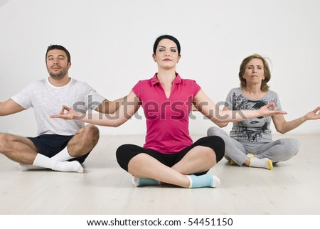 Group of people  doing yoga and sitting on floor in lotus position - stock photo