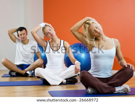 Group of people doing yoga exercise (focus on woman in the middle) - stock photo