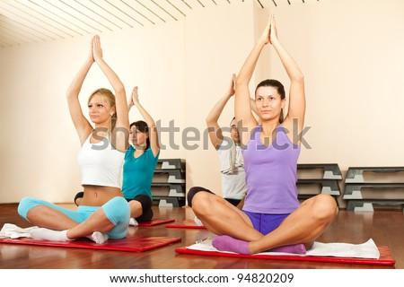 Group of people doing yoga on gymnastics mats - stock photo