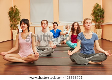 Group of people during yoga meditation breathing exercise class - stock photo