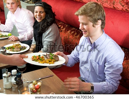 Group of people enjoying a rich dinner in a restaurant - stock photo