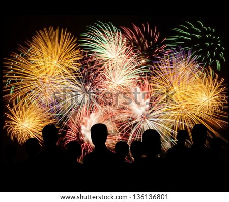 Group of people enjoying spectacular fireworks show in a carnival or holiday. People in silhouette. - stock photo