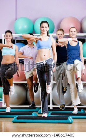 Group of people exercise at the gym on step boards in a fitness class - stock photo