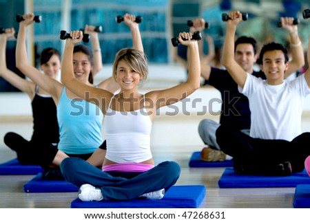 Group of people exercising at the gym with freeweights - stock photo