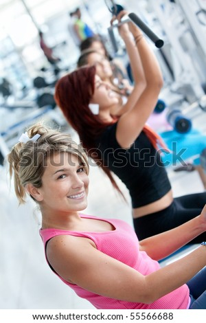 Group of people exercising with the machines at the gym - stock photo