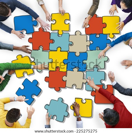 Group of People Forming Jigsaw Puzzles - stock photo