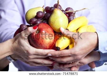 Group of people hands holding apples, oranges, grapes and bananas (selective focus) - stock photo