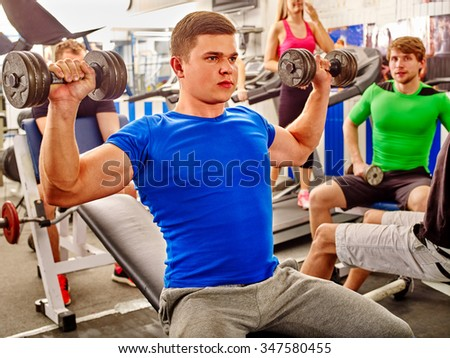 Group of people handsome man and beautiful women working with  dumbbells his body at gym.  - stock photo