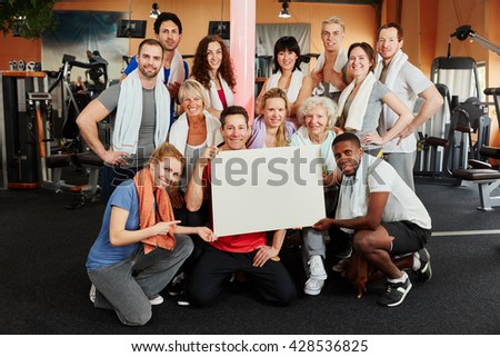 Group of people holding a white sign as advertising tool at the gym - stock photo