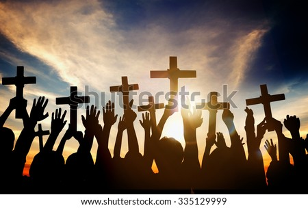 Group of People Holding Cross and Praying in Back Lit Concept - stock photo