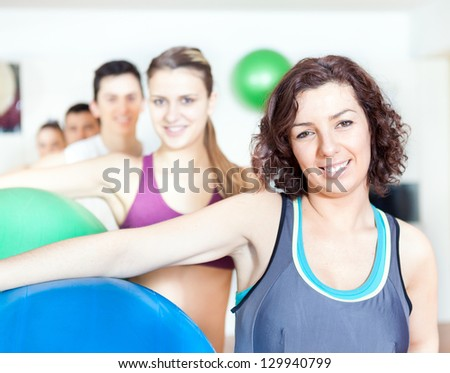 Group of people holding pilates ball at the gym - stock photo
