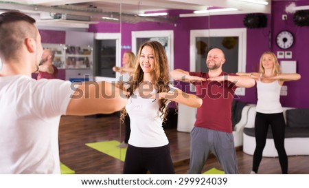 Group of people in a gym are doing fitness exercises - stock photo