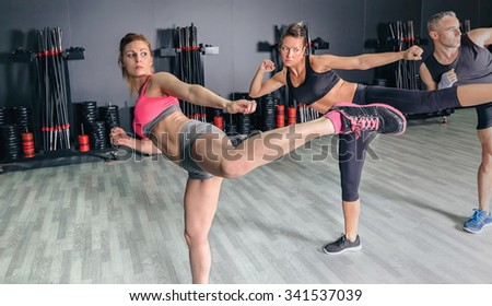 Group of people in a hard boxing class on gym training high kick - stock photo
