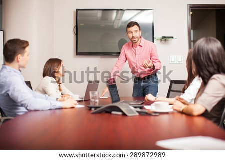 Group of people in a meeting room listening to a man presenting some ideas - stock photo