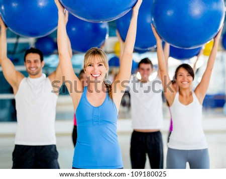 Group of people in a Pilates class holding a fitness ball - stock photo