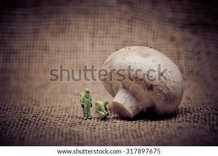 Group of people in protective suit inspecting a mushroom. Genetically modified food concept. Toned image - stock photo