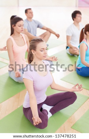 Group of people in the lotus position indoors - stock photo