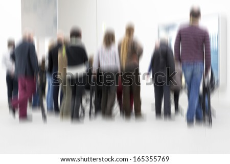 Group of people inside an exhibition hall, blurry - stock photo