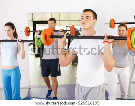 Group of people lifting barbells in weight training class with trainer in front.