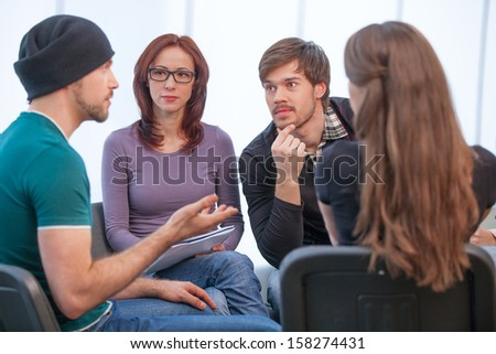 Group of people listening to what young man saying. Close up of several people in workshop  - stock photo