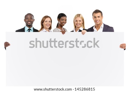 Group of people looking at camera on white background with white board - stock photo