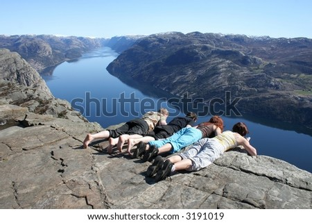 Group of people looking over the edge of Pulpit Rock in Norway. Lysefjorden is in the background. - stock photo