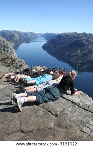 Group of people looking over the edge of Pulpit Rock in Norway. Lysefjorden is in the background.