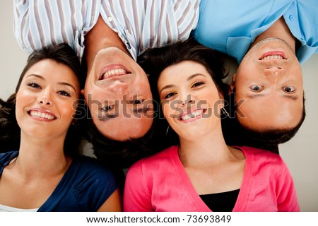 Group of people lying on the floor with heads together