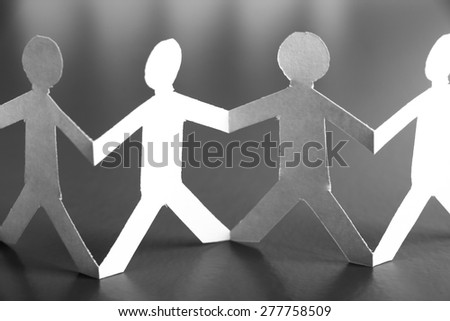 Group of people made of paper are holding hands together. Team concept. - stock photo