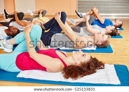 Group of people making a stretching exercise during pilatess class