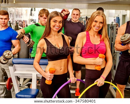 Group of people man with dumbbells  and woman holding hoop working  his body at gym.  - stock photo
