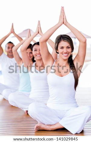 Group of people meditating in a yoga class - stock photo
