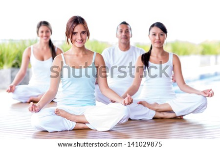 Group of people meditating in a yoga studio - stock photo