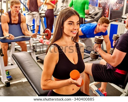 Group of people men and beautiful girls working with  dumbbells his body at gym.  - stock photo