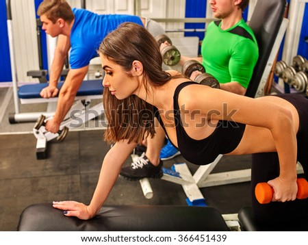 Group of people men and women harding working with  dumbbells his body at gym.  - stock photo